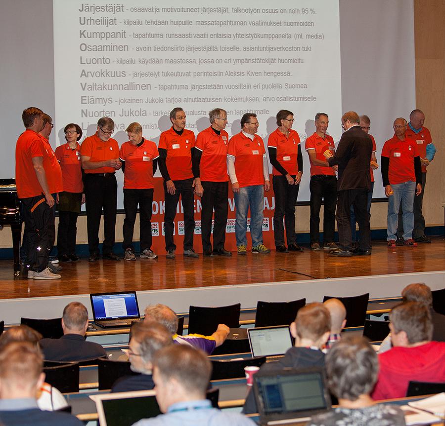 Oranssipaidat näyttämöllä - taustalle projisoitui sopivasti Kaukametsäläisten puheenjohtaja Juhani Sihvosen esittämät Jukolan arvot.
